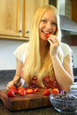 Woman eating a strawberry while cutting up fruit an attractive young tasting as she is chopping Royalty Free Stock Image