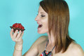 Woman eating a strawberry tartlet Royalty Free Stock Photo