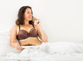 Woman eating sweet chocolate chip cookies smiling girl in bed at home Stock Photo