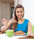 Woman eats buckwheat at home interior smiling with spoon Stock Photo
