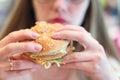 Woman eats fresh appetizing hamburger Royalty Free Stock Photo