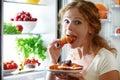 Woman eats night stole the refrigerator Royalty Free Stock Photo