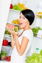 Woman eats watermelon near opened refrigerator the full of vegetables and fruit concept of healthy and dieting food Royalty Free Stock Image