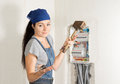 Woman electrician with a problem attractive young female standing in front of an open fuse box wooden mallet in one hand and Stock Photos