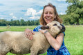 Woman embracing and hugging young sheep