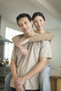 Woman embracing man from behind portrait of a women sitting on countertop and men Stock Photography