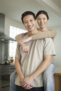 Woman embracing man from behind portrait of a women sitting on countertop and men Royalty Free Stock Images
