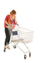 Woman with empty shopping cart red haired isolated over white background Stock Images