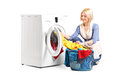 Woman emptying a washing machine isolated on white background Royalty Free Stock Images