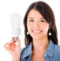 Woman with an energy saving bulb happy isolated over white background Stock Photo