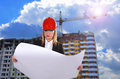 Woman engineer holding blueprint and standing on buildings background Stock Photography