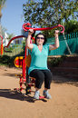 Woman enhancing her arms in fitness station mature the strength of upper limbs with outdoor seated push equipment Royalty Free Stock Image