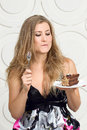 Woman enjoy cake eagerly looking at with a fork in his hand Stock Photos