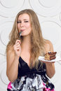 Woman enjoy cake eagerly looking at with a fork in his hand Stock Images