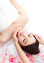 Woman enjoy receiving face massage at spa with roses beautiful young she is very relaxed asian beauty Stock Photography