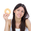 Woman enjoy sweet donut and looking at the corner.