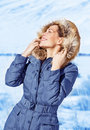 Woman enjoy winter nature happy with closed eyes enjoying sun light in cold frosty day wearing fashionable wintertime clothes Royalty Free Stock Photos