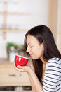 Woman enjoying the aroma of coffee at home with closed eyes Royalty Free Stock Photos