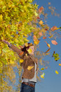 Woman enjoying autumnal falling leaves on a nice warm autumn day Royalty Free Stock Images
