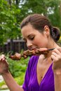 Woman enjoying barbecue outdoors tasty Royalty Free Stock Image