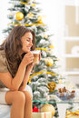 Woman enjoying coffee near christmas tree happy young latte macchiato Stock Photos