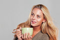 Woman enjoying a cup of tea isolated on grey Royalty Free Stock Images