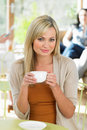 Woman enjoying drink in cafe portrait of sitting smiling Royalty Free Stock Images