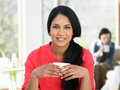 Woman enjoying drink in cafe smiling to camera Stock Images
