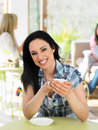 Woman enjoying drink in cafe smiling to camera Royalty Free Stock Image