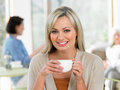 Woman enjoying drink in cafe smiling to camera Stock Photography