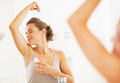 Woman enjoying freshness after applying roller deodorant on underarm Royalty Free Stock Photography