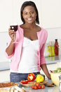 Woman Enjoying Glass Of Wine In Kitchen Royalty Free Stock Photo