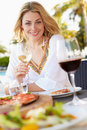Woman enjoying meal in outdoor restaurant smiling Stock Image