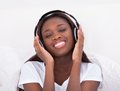 Woman enjoying music through headphones in bed happy african american at home Royalty Free Stock Images
