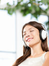 Woman enjoying music in headphones at home relaxed relaxing girl sitting sofa listening to with earphones with eyes Royalty Free Stock Images