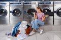 Woman enjoying music in laundry young with basket while sitting at laundromat Stock Photos