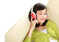 Woman enjoying music young attractive with headphone on the couch Stock Photography