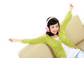 Woman enjoying music young attractive with headphone on the couch Royalty Free Stock Photo