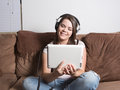 Woman enjoying streaming wireless entertainment at home mobile media while using large headphones sitting on couch relaxing Stock Image