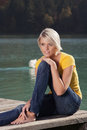Woman enjoying a summer day at the lake beautiful carefree barefoot young with short blond hairstyle sitting on wooden jetty Royalty Free Stock Photo