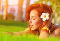 Woman enjoying summer nature profile of attractive with closed eyes dreaming outdoors lying down on fresh green grass glade Stock Photo
