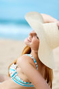 Woman enjoying the sun at the beach beautiful smiling young in sunhat Royalty Free Stock Images