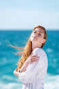 Woman enjoying the sunshine at the beach standing with her head tilted to sun and eyes closed against an ocean backdrop Royalty Free Stock Images