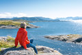 Woman enjoying view at fjord norwegian landscape back of a kvernesfjorden with clouds floating over water Royalty Free Stock Images