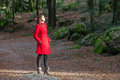 Woman enjoying the warmth of the winter sunlight on a forest wearing red overcoat Royalty Free Stock Photography