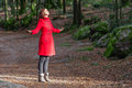 Woman enjoying the warmth of the winter sunlight on a forest wearing red overcoat Stock Image