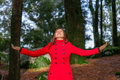 Woman enjoying the warmth of the winter sunlight on a forest wearing red overcoat Stock Images
