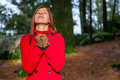 Woman enjoying the warmth of the winter sunlight on a forest wearing red overcoat Royalty Free Stock Image