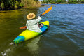 Woman enjoys quality time in her kayak a straw hat paddles away from shore on a beautiful river or lake Royalty Free Stock Image