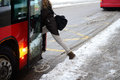 Woman entering bus in winter young from sidewalk Royalty Free Stock Photography